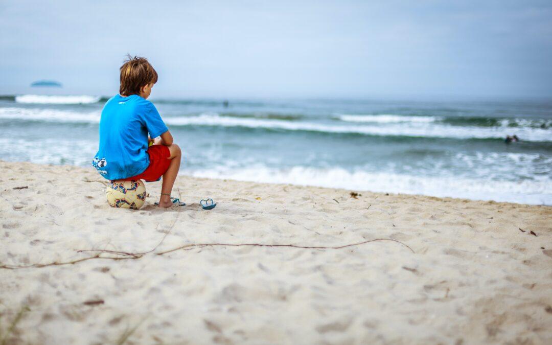 boy with soccer ball on the beach