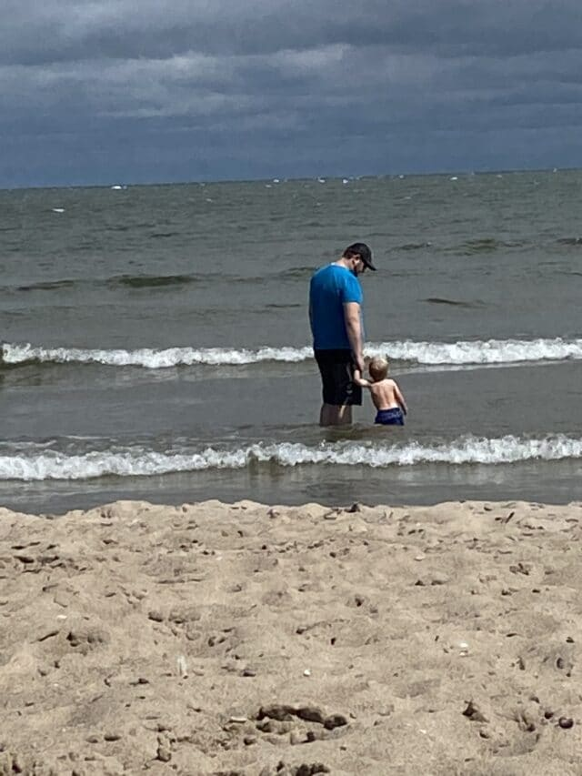 Photo of toddler and dad in the water at the beach