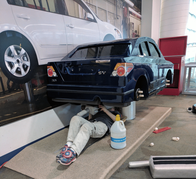 kid under car fixing it - Best museums in Nashville for Kids