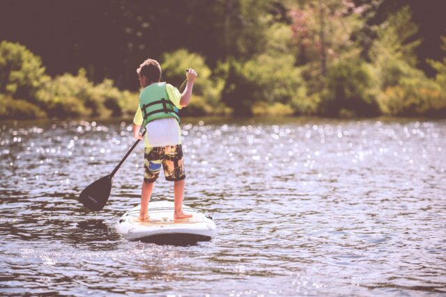 A young boy in a green life vest, shown from behind, stand-up paddle boards on a lake. Kid-friendly fun at Lake Natoma involves stand-up paddle boarding and kayaking