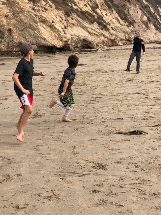 Boys throwing football on beach - The beautiful coastal city of Santa Barbara has lots of fun adult activities but there is a lot of fun to be had in Santa Barbara with kids!