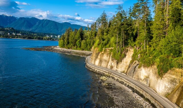 Aerial view of the Stanley Park seawall, coniferous terrain on one side and the ocean on the other. vancouver with kids how to spend the best long weekend family travel