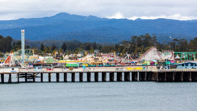 Santa Cruz Boardwalk, shown from the ocean, with mountains in the background. Best things to do with kids in Santa Cruz family travel