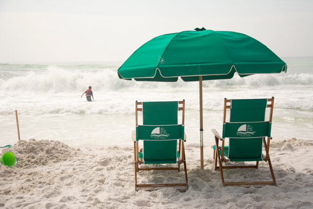 Green beach chairs and a matching umbrella with the ocean in the distance. A child is playing in the waves. One last beach visit is a great recipe for Labor Day fun.