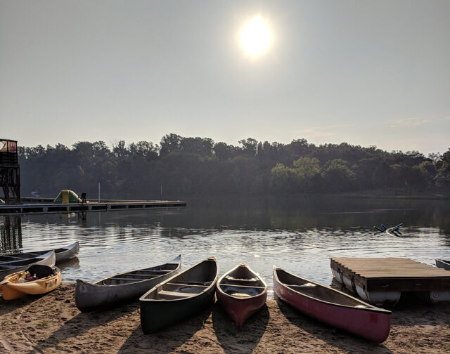 Empty canoes on the edge of a lake at sunrise. Plan an outdoor adventure for Labor Day fun.