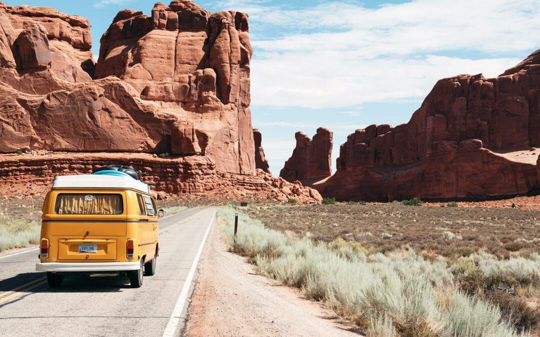 A yellow van drives towards red rock formations and a blue sky. Labor Day Fun.