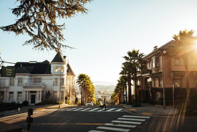 A beautiful San Francisco street corner with palm trees and old buildings. Explore a new city for Labor Day fun and a weekend vacation.