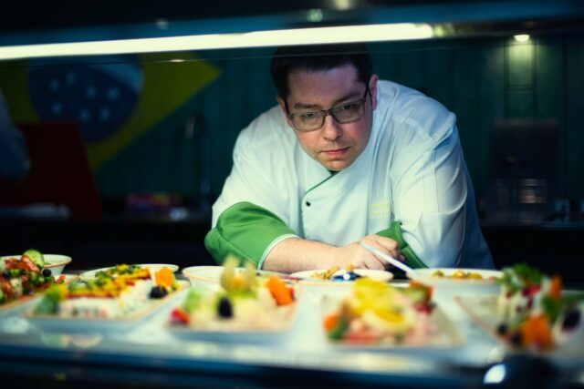 A chef stands and looks at plates of food. managing food allergies while on vacation