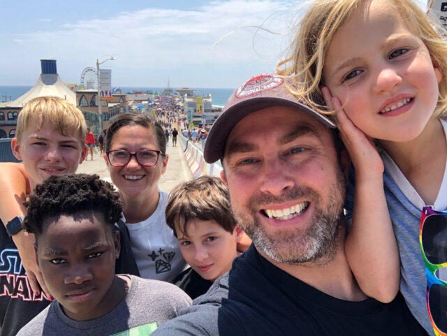 Travel tips for helping kids with vacation anxiety. Two parents and four kids stand on a pier in California during their vacation.