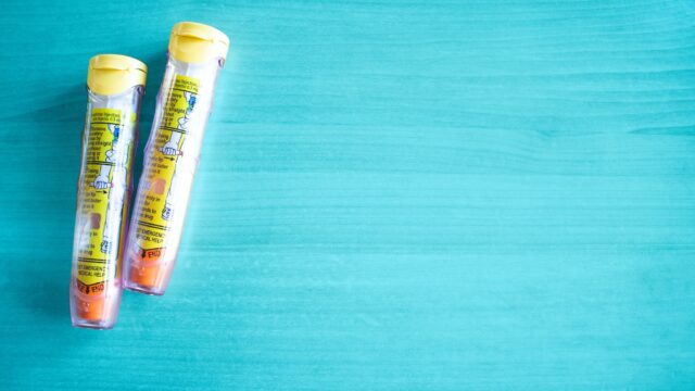 two epinephrine auto-injections, against a baby blue backdrop. managing food allergies while on vacation