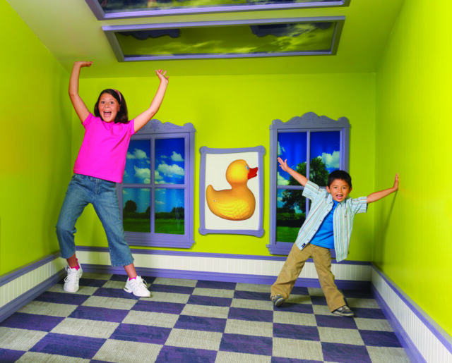 photo of kids playing in slanted house - ROCHESTER New York is full of fun things to do for kids of all ages. Here are the best ones like Niagra Falls, Genesse Country Village and the Seneca Park zoo.