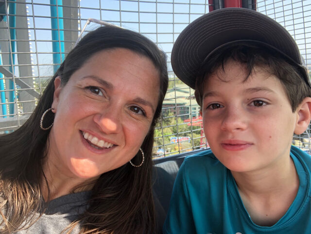 A mom and son at the top of a ferris wheel. Vacation anxiety and travel anxiety require slowing down and listening.