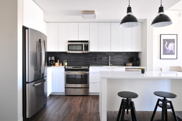 a kitchen with wooden floors and white cabinets and tabletops. managing food allergies while on vacation