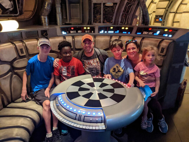 A family sits in the Millenium Falcon at Disneyland during their family vacation. Parents can work together to help kids with anxiety when traveling.
